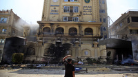An Egyptian protester looks at the damaged Muslim Brotherhood headquarters in Cairo. Protesters stormed and ransacked the headquarters early Monday, in an attack that could spark more violence as demonstrators gear up for a second day of mass rallies.