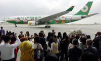 "Local journalists take photos of EVA airplane decorated with ""Hello Kitty"" during a press preview in Taoyuan in 2005."