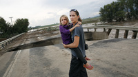 Samantha Kinzig of Longmont, Colo., and her daughter Isabel, 5, took a close look at a damaged bridge in Longmont Friday. Heavy rains that fueled widespread flooding in numerous Colorado towns have eased, but forecasters predict more on Saturday and Sunday.
