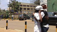 Women hug outside the upscale Westgate shopping mall in Nairobi, seen in the background, where gunmen attacked around midday Saturday.