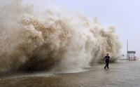 A man runs from a huge wave pushed up by Typhoon Usagi on a wharf in China's Guangdong province Sunday. Usagi killed at least 25 people after crashing ashore in southern China.