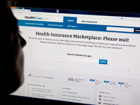 A woman looks at the HealthCare.gov insurance exchange internet site October 1, 2013.