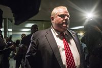 Toronto Mayor Rob Ford leaves his office after councilors passed motions Monday to limit his powers.