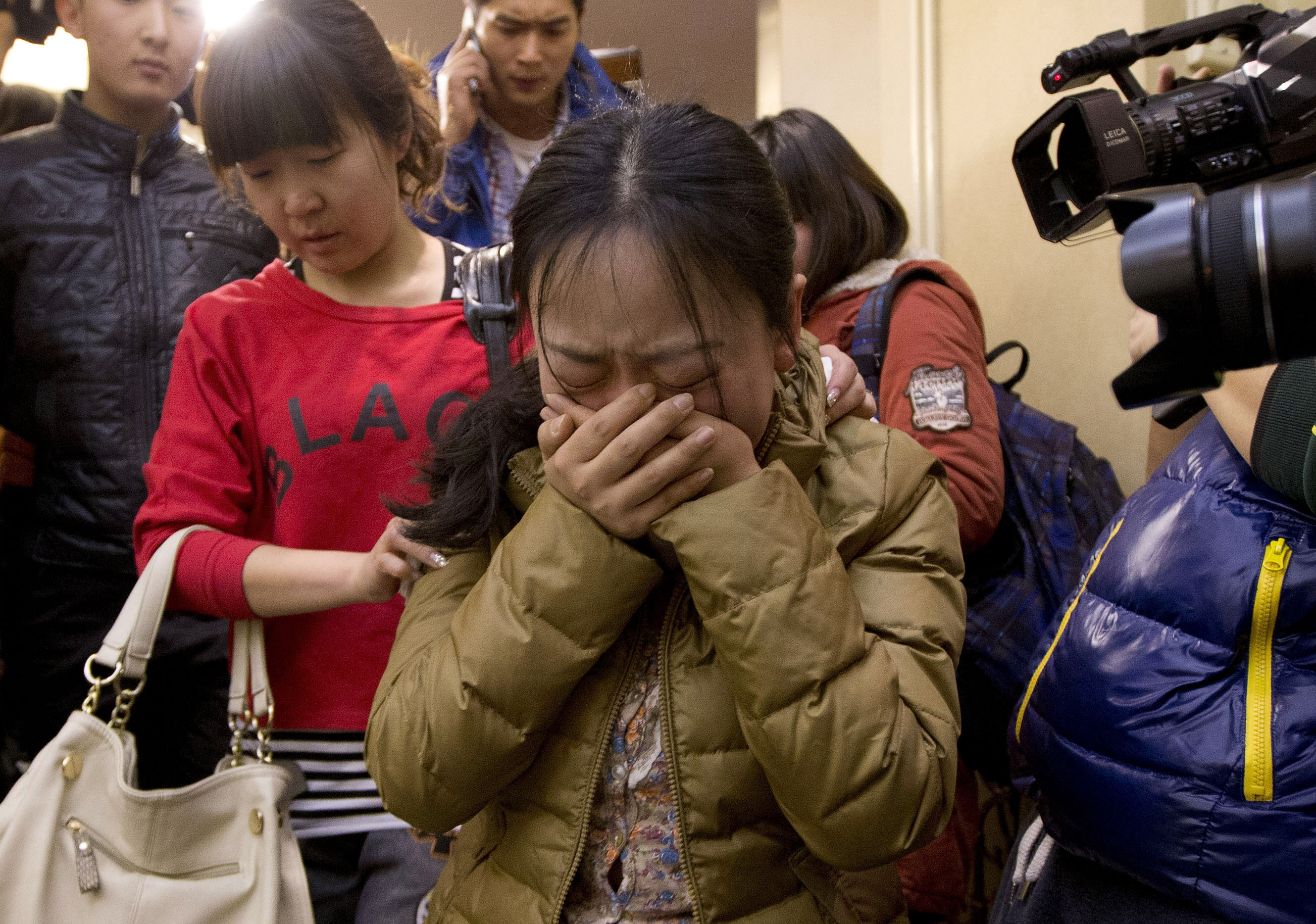A relative of passengers aboard a missing Malaysia Airlines flight is escorted by a woman from a Beijing hotel room for loved ones of those aboard the airplane Sunday.