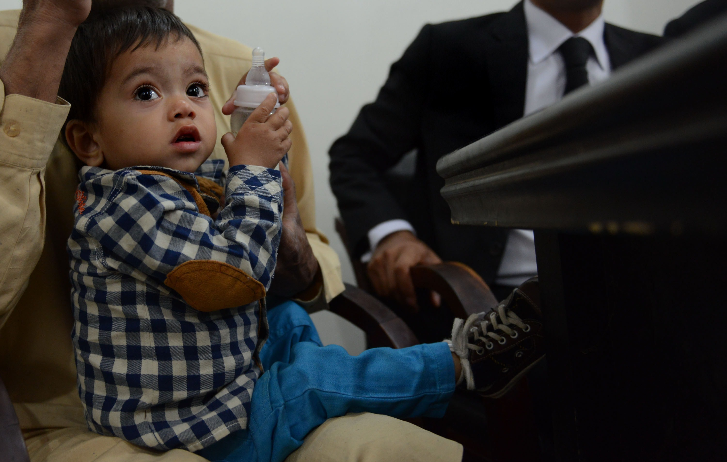 Pakistani toddler Mohammad Musa, seen here sitting in his grandfather Muhammad Yasin's lap at a court hearing in Lahore. A court threw out charges of attempted murder against the toddler Saturday.