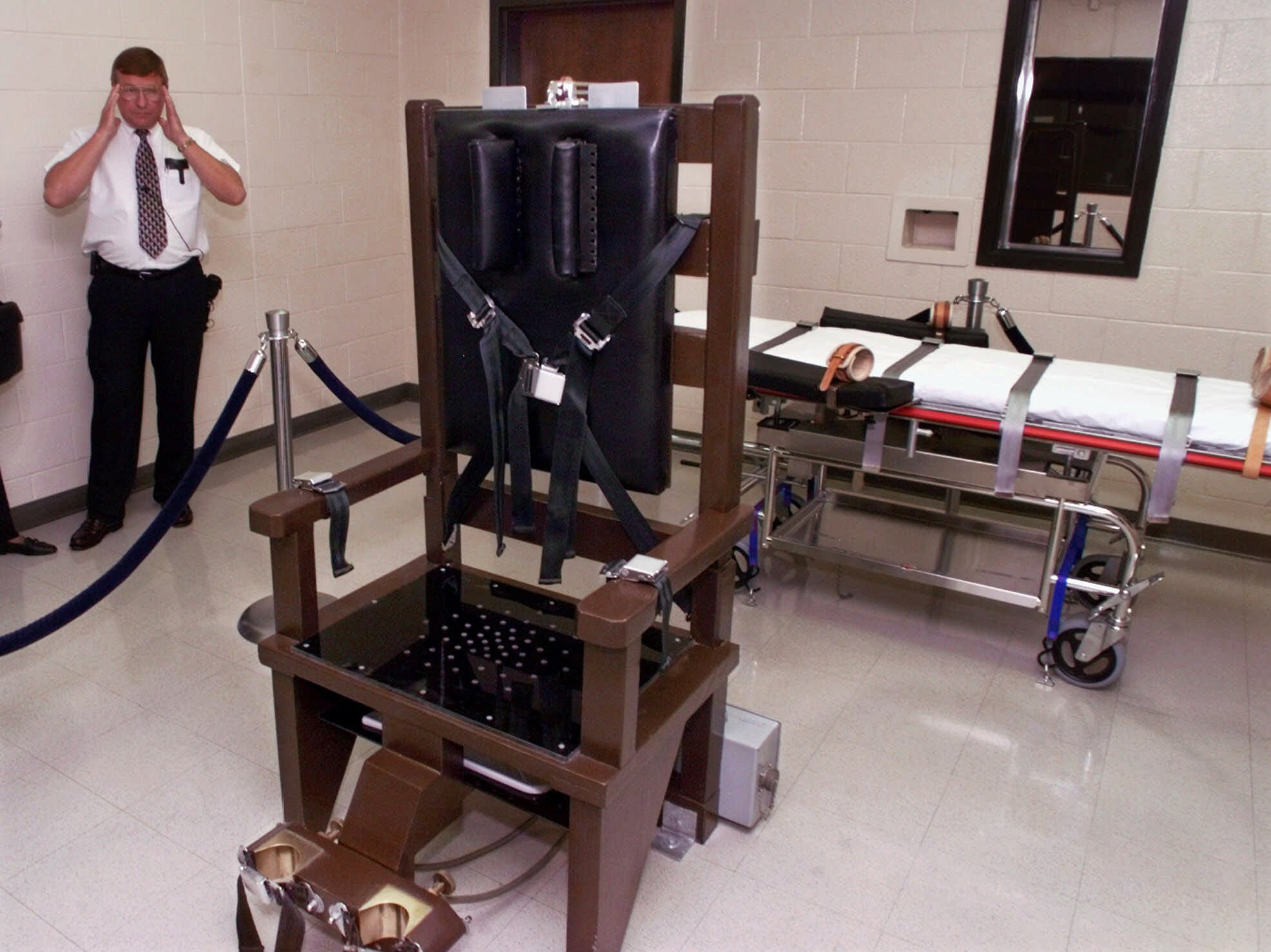 A warden at Riverbend Maximum Security Institution in Nashville, Tenn., is shown in the prison's execution chamber in 1999. The electric chair is shown next to a lethal injection gurney.