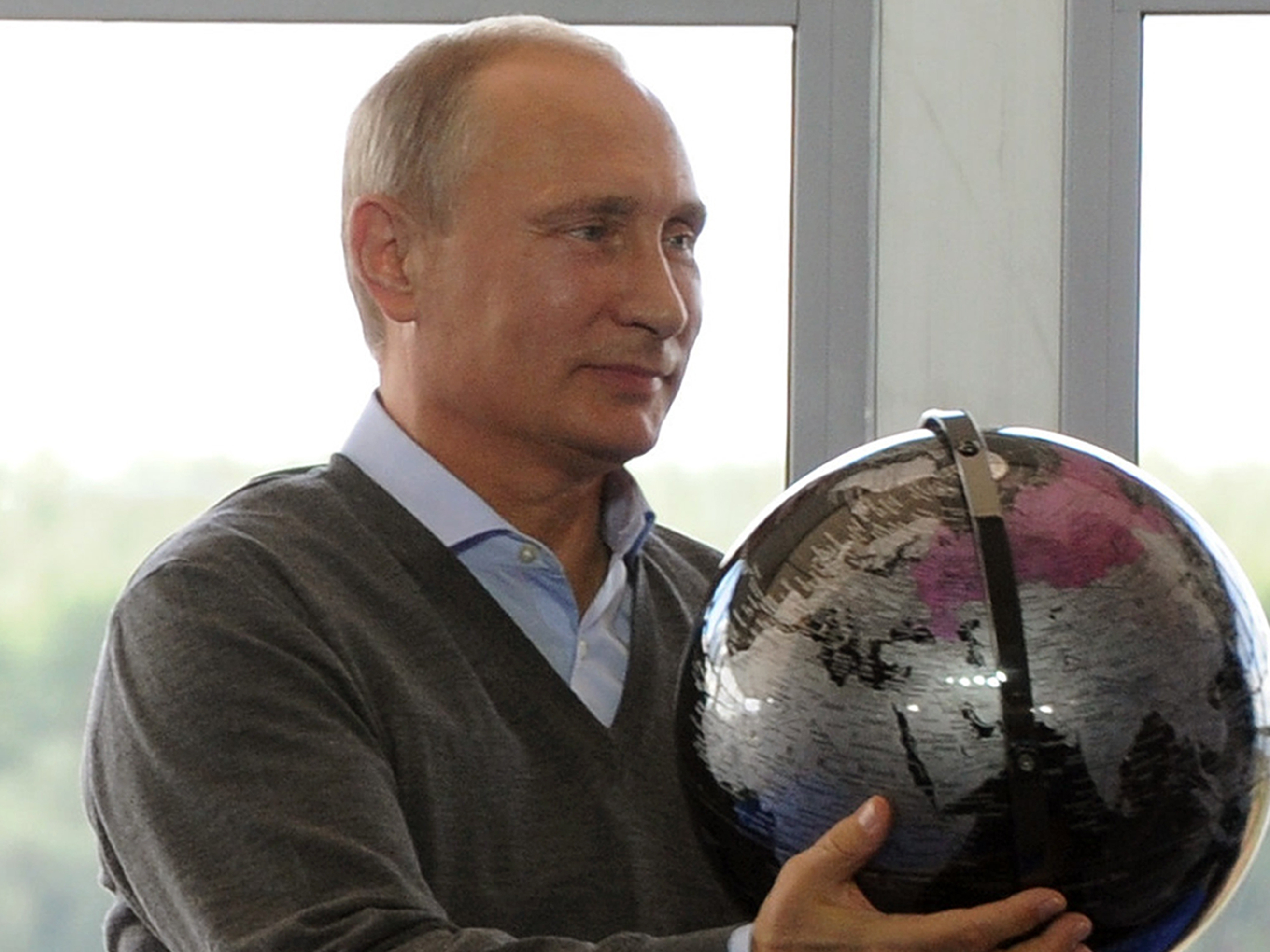 Russian President Vladimir Putin holds a terrestrial globe presented him as a gift in Tver region, Russia, on Friday.