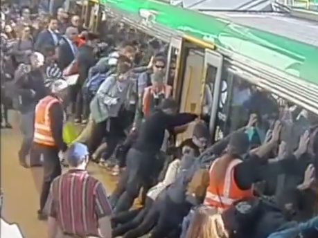 Train passengers tilt a train to free a fellow rider.