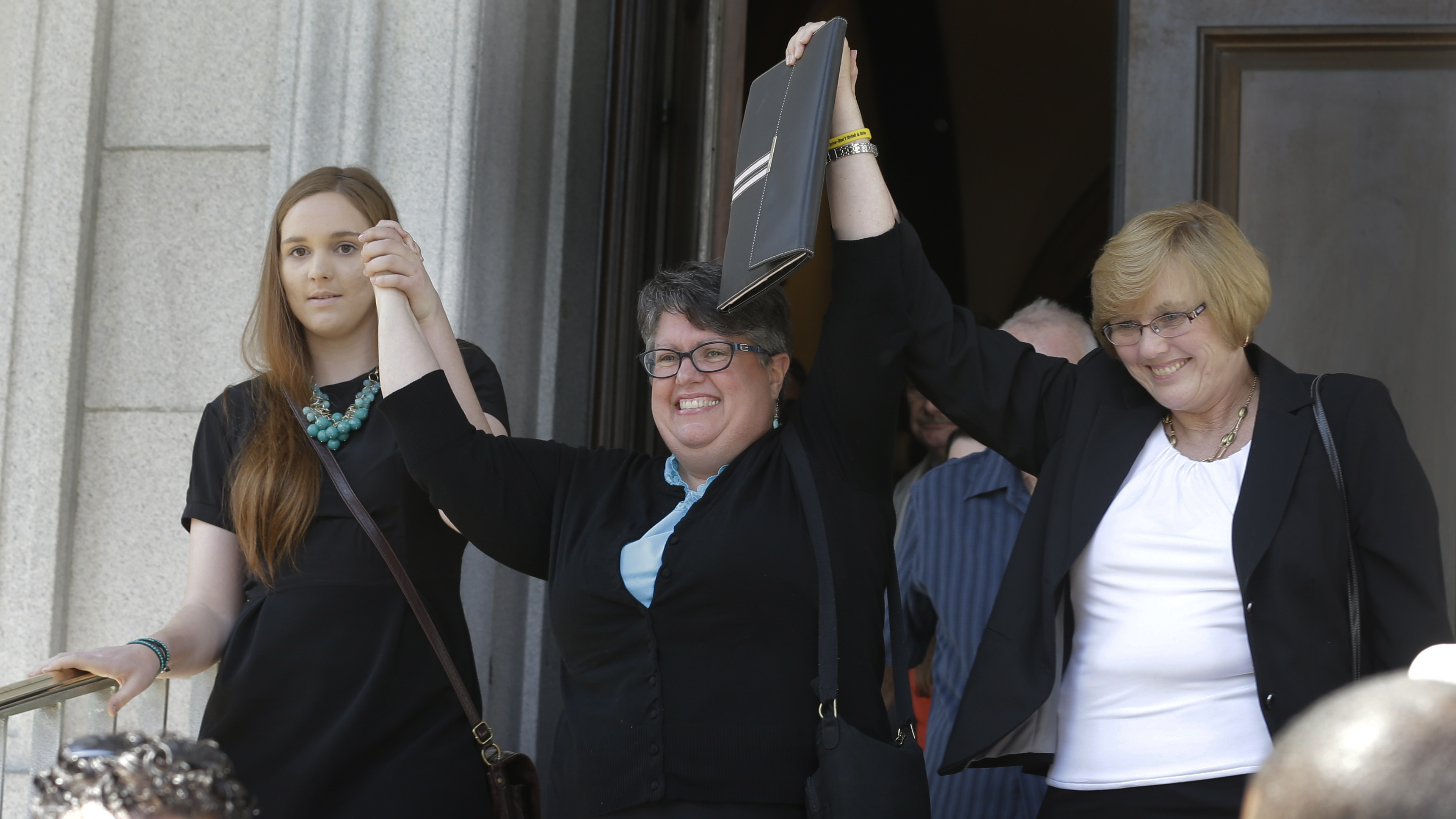 Plantiffs in the federal suit over Virginia's ban on gay marriage, Emily Schall-Townley (from left), Carol Schall and Mary Townley, raise their arms after a hearing on Virginia's same sex-marriage ban in Richmond, Va., in May. Today, the 4th U.S. Circuit Court of Appeals refused a motion to stay its decision that the ban isn't constitutional.