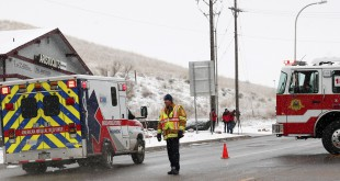 An ambulance proceeds Friday up a secured road leading to a Planned Parenthood center in Colorado Springs, Colo., after reports of an active shooter.