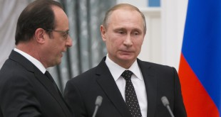 Russian President Vladimir Putin (right) listens to French President Francois Hollande as they leave their news conference in Moscow on Thursday.