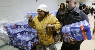 R&B singer Kem helps Mwamini Wallace carry bottled water to her vehicle in Flint, Mich., last month.