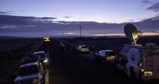 Media wait at a checkpoint about 4 miles from the Malheur Wildlife Refuge Headquarters near Burns, Ore., as the sun rises on Thursday. The FBI had surrounded the last four protesters holed up at a federal wildlife refuge in Oregon and were waiting for them to surrender.