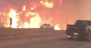 A photo provided by Tyler Burgett shows a wildfire's flames along Highway 63 in Fort McMurray, Alberta, earlier this week. Some people who fled the town have now been ordered to move again, in a new evacuation.