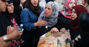 Suha (center), the mother of murdered Palestinian teenager Mohammed Abu Khdeir, takes part in a protest outside the district court in Jerusalem on Tuesday. She's holding a picture of her son.