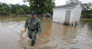 West Virginia State Trooper C.S. Hartman walks from a shed that he checked out as he and other crews search homes on Saturday in Rainelle, W. Va.