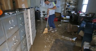 Shane Altzier sweeps out the mud from the utilities office in Rainelle, West Virginia, one of the towns hardest hit by floods that tore through the state on Friday. More rain this week has slowed down clean-up efforts.