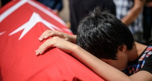 A child leans on the coffin of his uncle, Habibullah Sefer, on Thursday. Sefer, along with more than 40 other people, was killed in a suicide attack on Tuesday at the Ataturk airport in Istanbul.