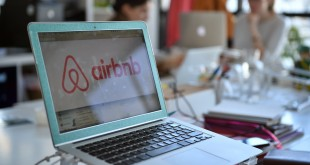 The logo of online lodging service Airbnb is shown on a screen in the Airbnb offices in Paris in 2015.