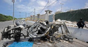 Somali soldiers stand guard next to wreckage from a car bomb outside the U.N.'s office in Mogadishu on Tuesday. At least 13 people were killed in twin bombings near U.N. and African Union buildings adjoining Mogadishu's airport, police said, in what the jihadist al-Shabab group claimed as a suicide attack.