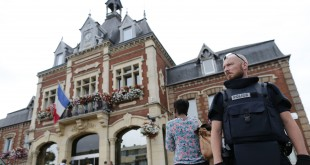 A French police officer stands guard by Saint-Etienne-du-Rouvray's city hall after a priest was killed and hostages taken at a church in the small town on Tuesday. Police say they killed two hostage-takers in the attack in the Normandy town, 77 miles north of Paris.