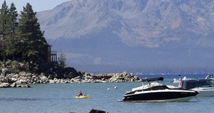A kayaker paddles along Zephyr Cove, near the site of the 20th Annual Lake Tahoe Summit in south Lake Tahoe, Nev. President Barack Obama said the environmental challenges of conservation and fighting climate change are inseparably linked.