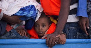 A boy is crowded among more than 700 migrants on a wooden boat before being rescued about 13 miles north of Sabratha, Libya. The boat was one of 40 vessels rescued on Monday.
