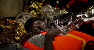 A refugee from Eritrea rests on a ship operated by the Italian navy after being rescued from the Mediterranean sea, about 13 miles north of Sabratha, Libya, on Monday.