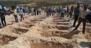 People wait close to empty graves at a cemetery on Sunday, during the funeral for the victims of a suicide attack on a wedding party in Gaziantep, Turkey. At least 50 people were killed when a suspected suicide bomber linked to Islamic State jihadists attacked a wedding thronged with guests, officials say.