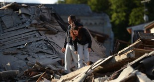 Residents stand among damaged buildings after a strong earthquake hit Amatrice on Wednesday. Central Italy was struck by a powerful, 6.2-magnitude earthquake in the early morning.