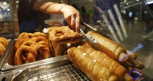 "A worker serves a ""pretzel dog"" at Auntie Anne's at a shopping mall in Kuala Lumpur, Malaysia, on Tuesday."