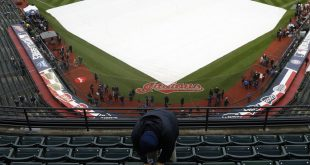 A worker wipes down the rain covered seats at Progressive Field in Cleveland before Game 2 of the World Series between the Cleveland Indians and the Chicago Cubs.
