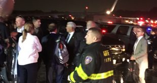 Republican presidential candidate Indiana Gov. Mike Pence, center, talks on the tarmac at New York's LaGuardia Airport after his campaign plane slid off the runway while landing Thursday.
