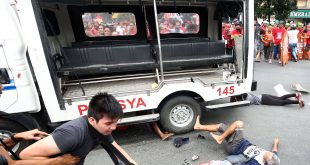 Protesters lie on the ground after being hit by a police van during a rally in front of the U.S. Embassy in Manila on Wednesday. A Philippine police van rammed and ran over several protesters.
