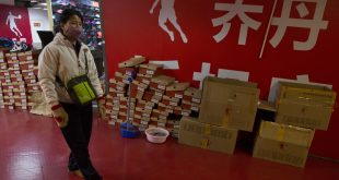 A shopper walks past a Qiaodan Sports retail shop on Thursday in Beijing, China.