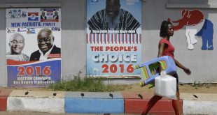 A woman walks past campaign posters of opposition presidential candidate Nana Akufo-Addo of the New Patriotic Party on Thursday in Accra, Ghana.