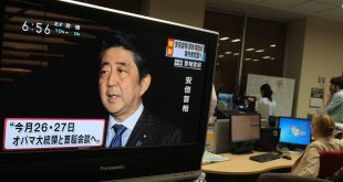 Local television news displays Japan's Prime Minister Shinzo Abe speaking to reporters at his official residence in Tokyo on Monday, as he announced he will become the first Japanese prime minister to visit Pearl Harbor.