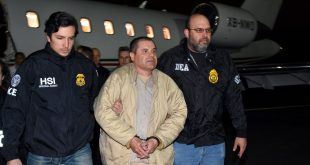 "Authorities escort Joaquin ""El Chapo"" Guzman (center) from a plane to a waiting caravan of SUVs at Long Island MacArthur Airport on Thursday in Ronkonkoma, N.Y."