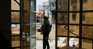 A member of the Iraqi special forces' Counter-Terrorism Service stands guard next to a damaged building at Mosul university on Sunday, during an ongoing military operation against the Islamic State.