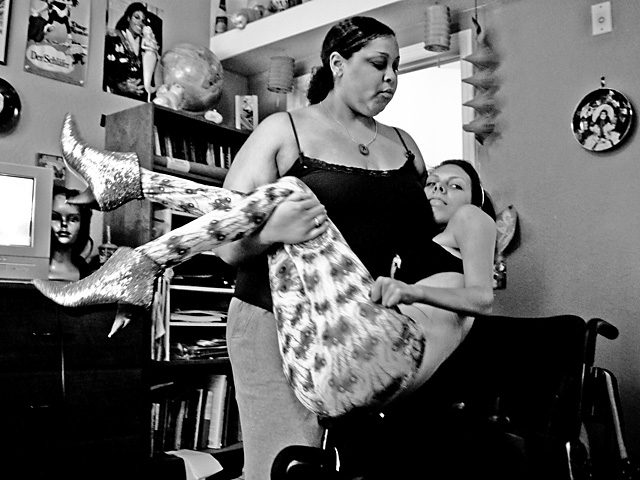 A personal assistant lifts Meaghan, wearing her favorite boots, from her bed.