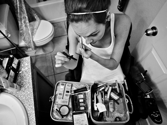 In her bathroom, Meaghan puts on make-up in preparation for her annual celebration party.