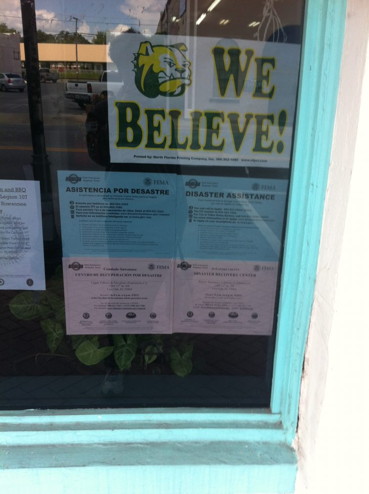 Disaster assistance information posted inside downtown business window in Live Oak, FL
