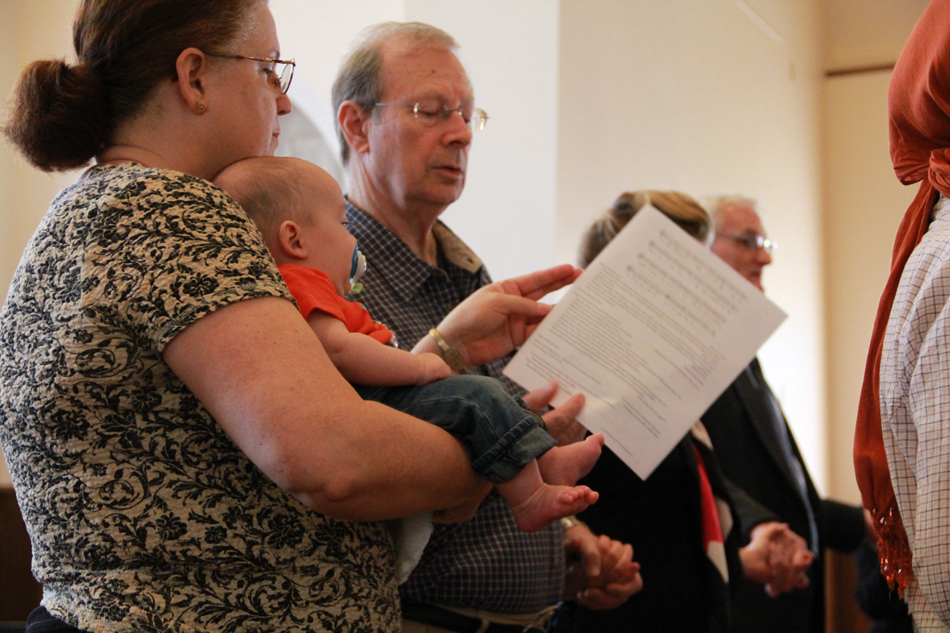 Virginia Mance, her 4-month-old grandson and husband Robert Mance participate in a Sept. 11, 2012, service at the Holy Trinity Episcopal Church in Gainesville.