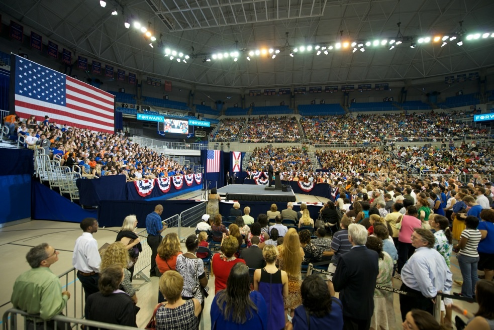A crowd listens to Gainesville mayor Craig Lowe before Michelle Obama's speech Monday at the O'Connell Center.