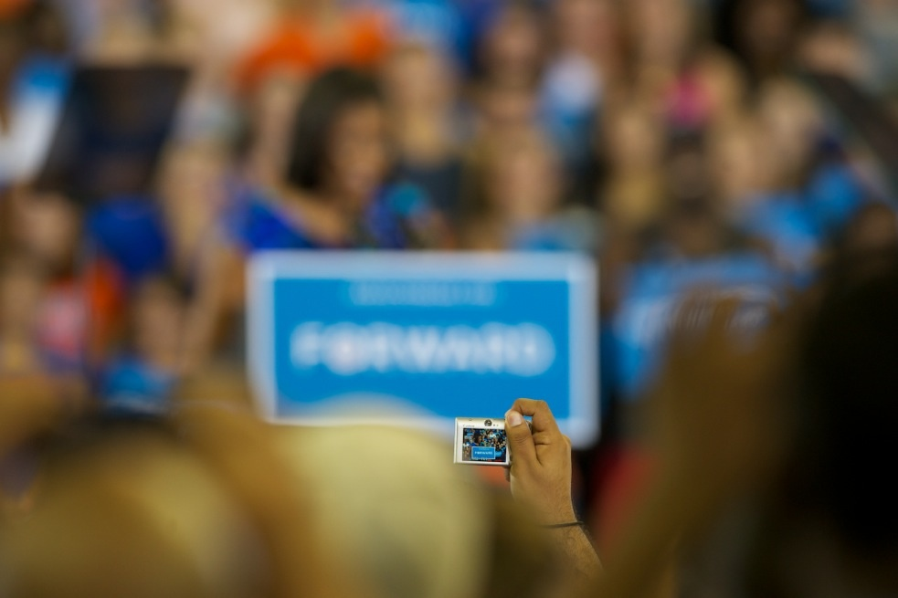 A speech attendee takes a photo of First Lady Michelle Obama on Monday at the O'Connell Center.