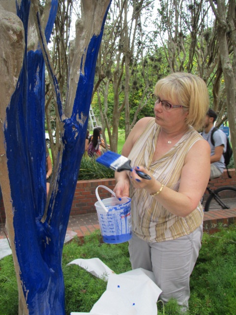 Adele Dimopoulos, the wife of artist Konstantin Dimopoulos, helps her husband paint trees outside of the Reitz Union on Monday afternoon.