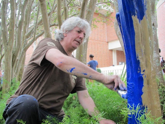 "Australian artist Konstantin Dimopoulos paints a tree outside of the University of Florida Reitz Union as part of his ""The Blue Trees"" exhibit. Dimopoulos's goal for the project is to make viewers take notice of trees that they would typically ignore and become more aware of environmental issues such as deforestation."