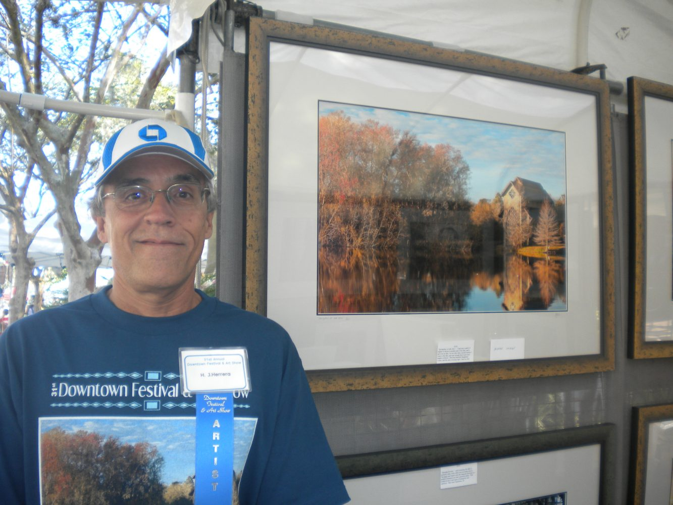 H.J. Herrera in front of the poster image for the 2012 Gainesville Festival & Art Show.
