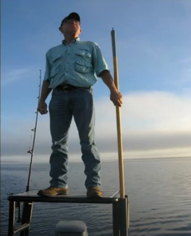 Johnny Bass stands on the back of a 20-foot-aluminum boat looking for gators.  He has more than 15 years of experience hunting them.