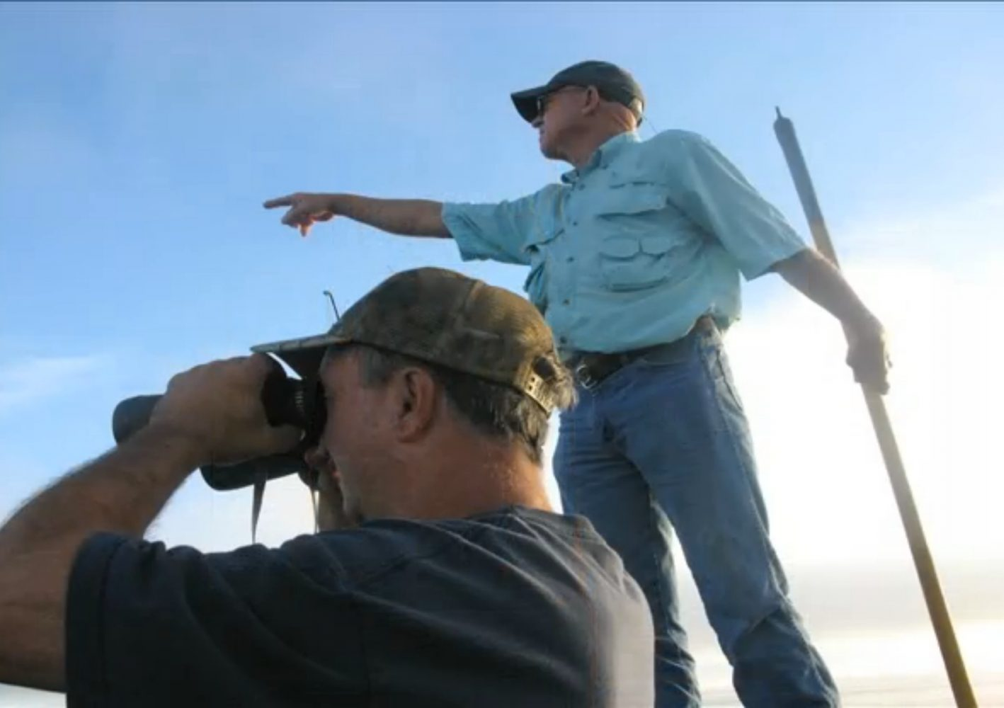 Bass points to the gator he has spotted.  John Kurtz looks through binoculars to decide if the alligator is large enough to go after.